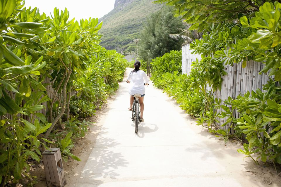 A woman riding a bike down a tropical path