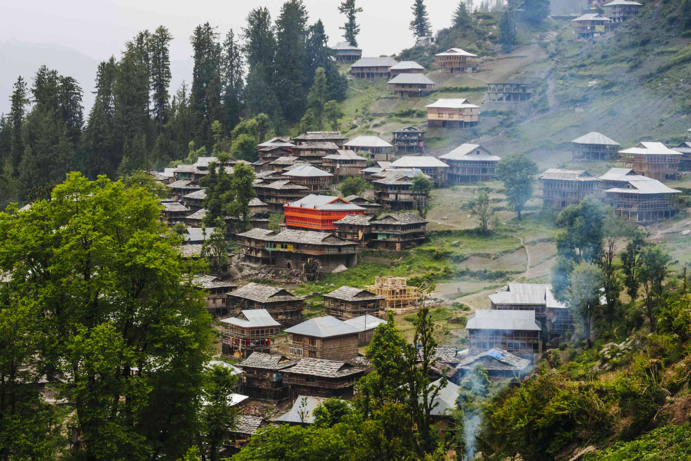 houses on a hillside with smoke in the foreground