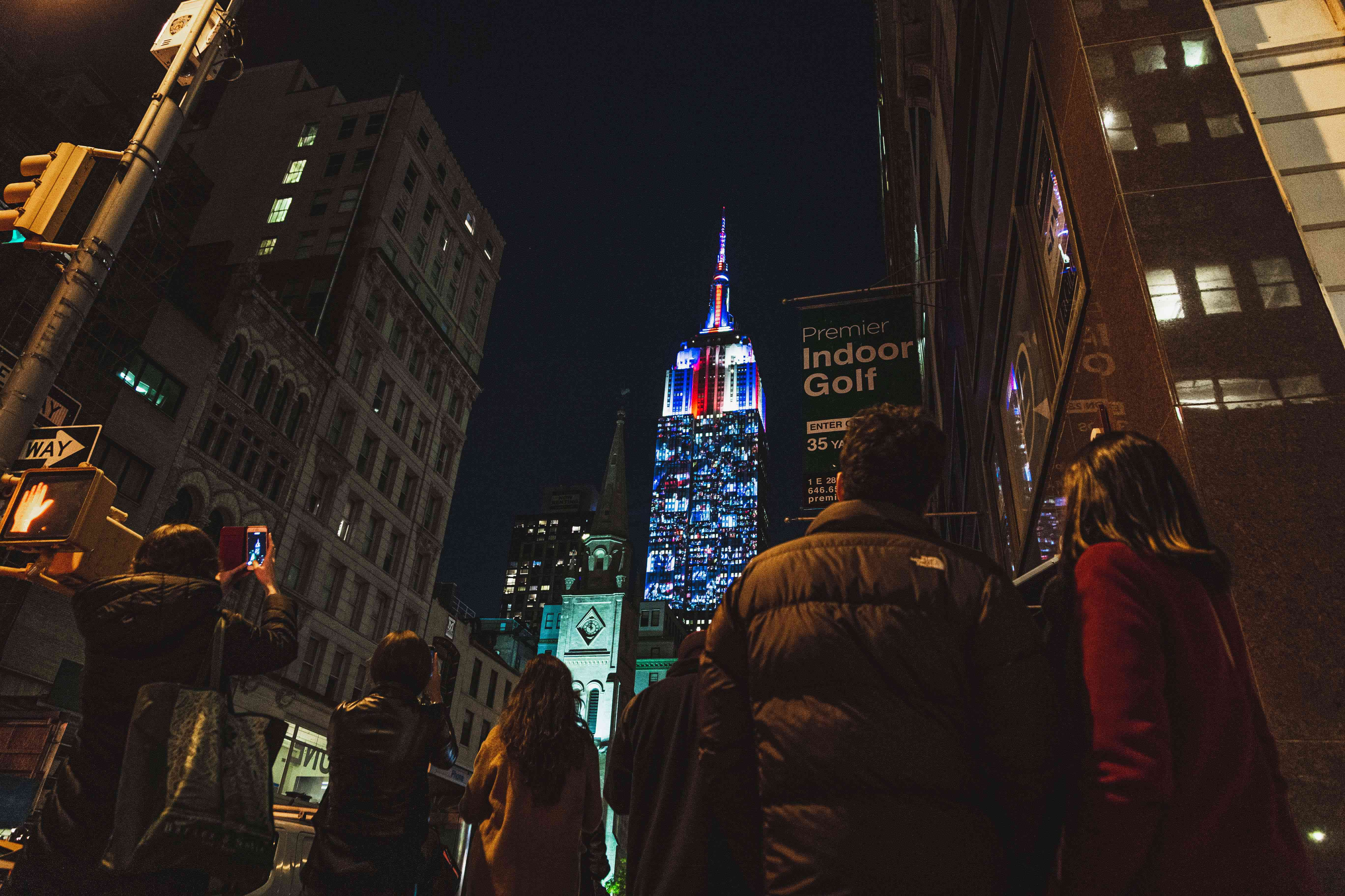 People looking up at the empire state building lit up at night
