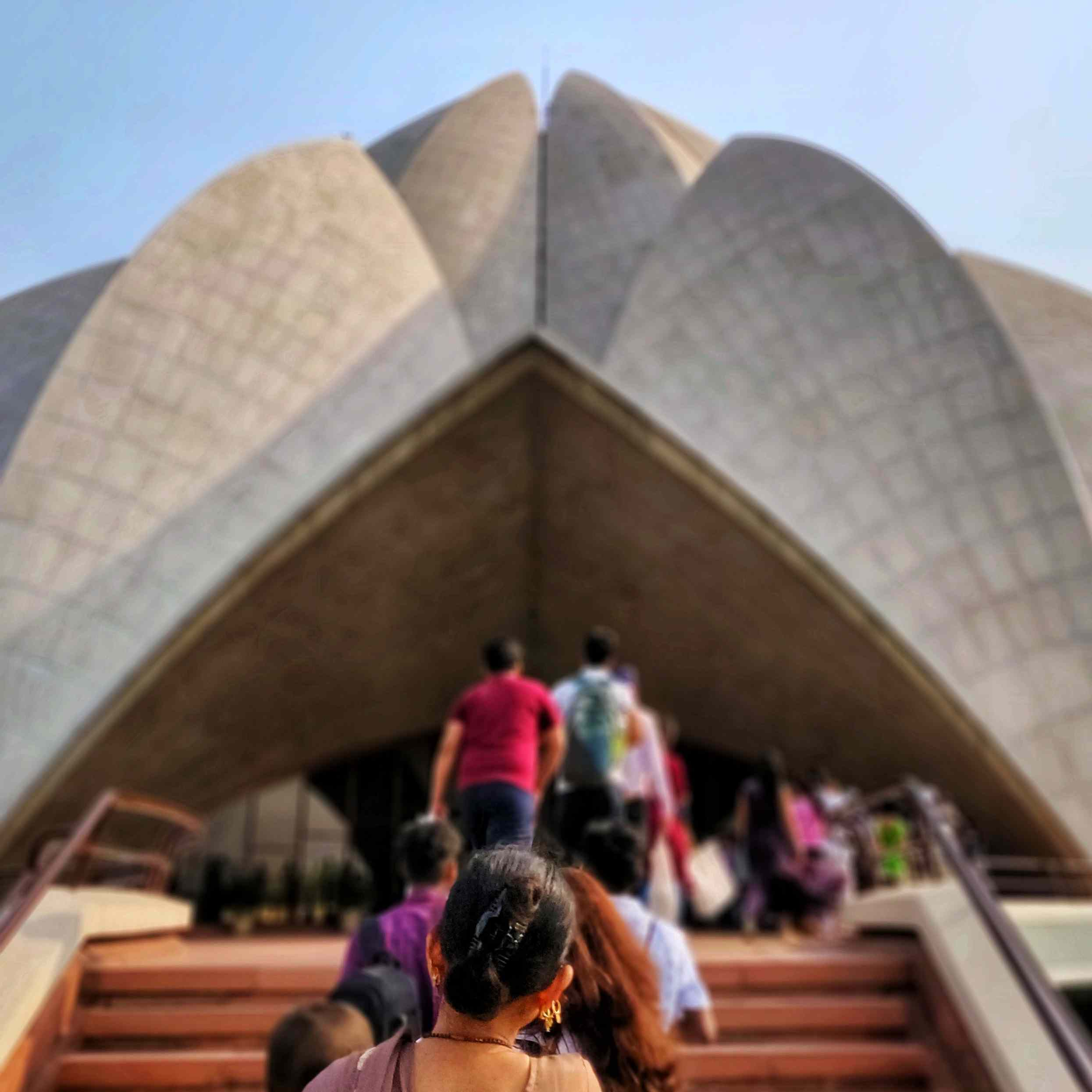 A line of people waiting to enter the lotus temple