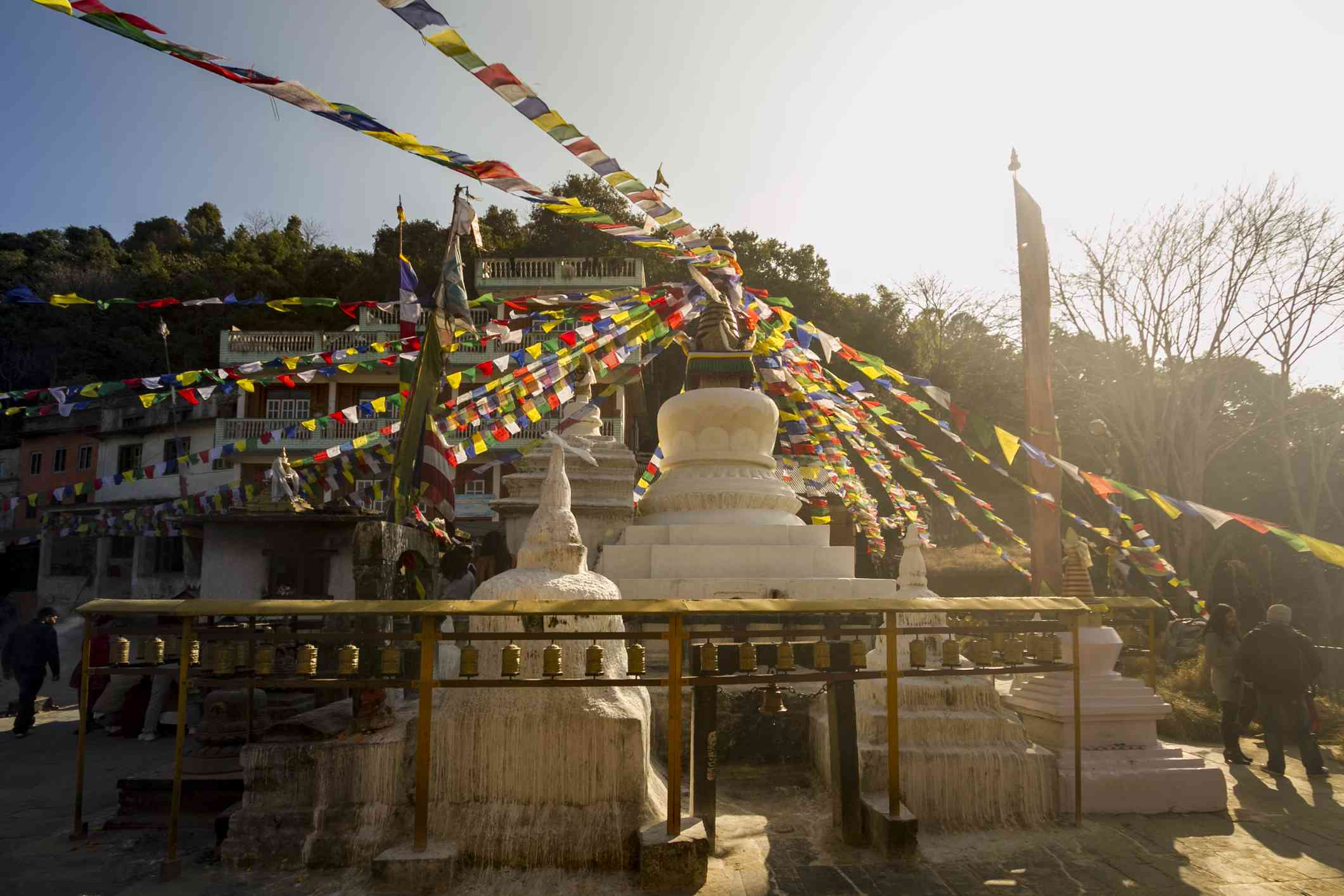 small white Buddhist stupas with colorful Tibetan prayer flags