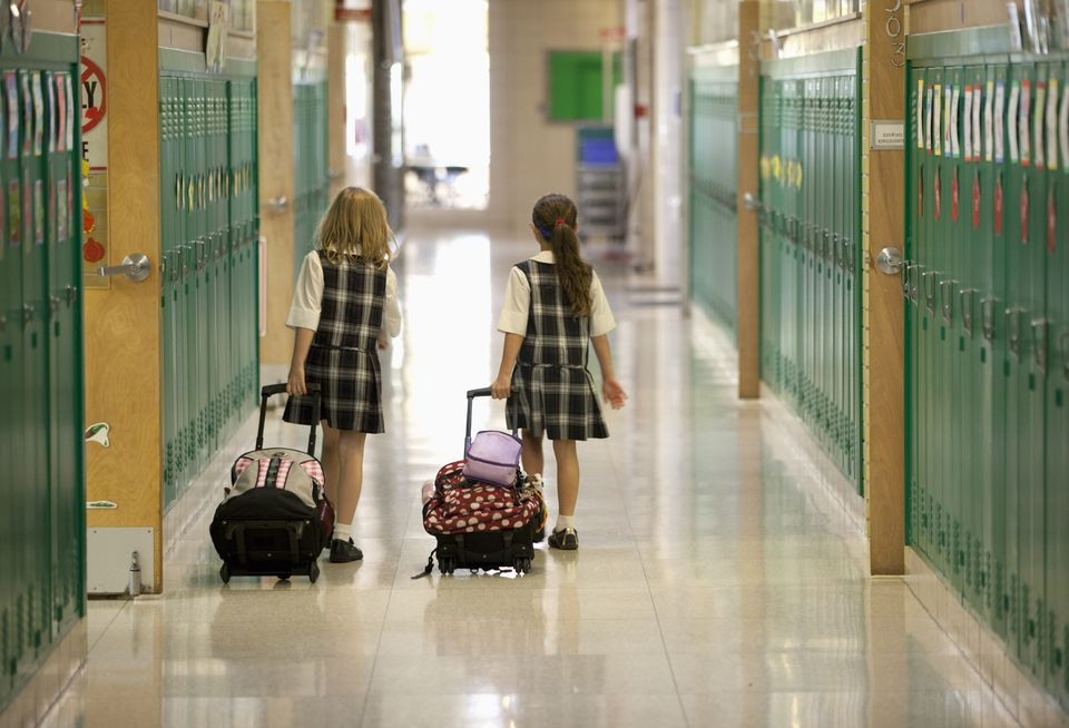 Second grade girls roll backpacks in school