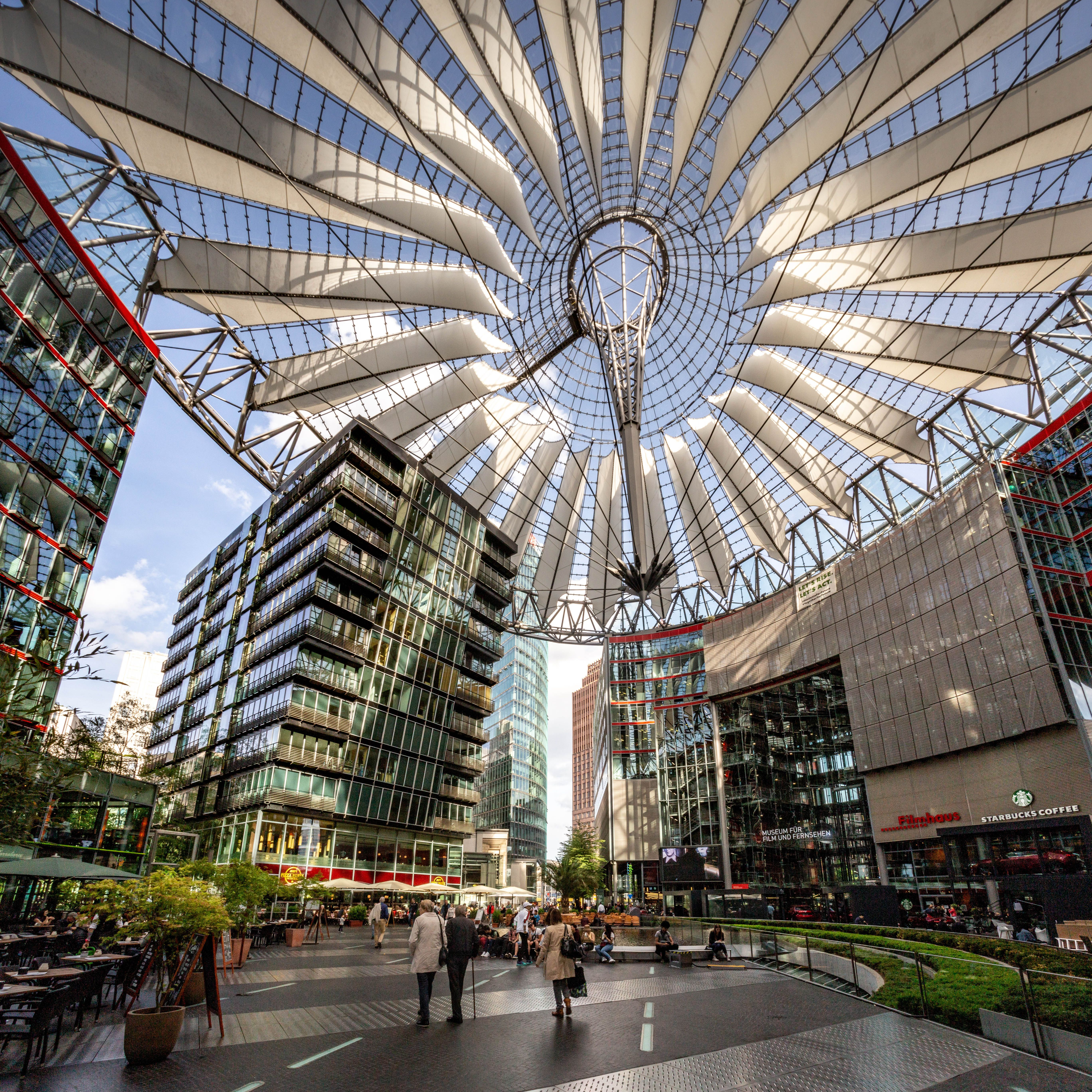 A shot of Potsdamer Platz with a large outdoor sculpture above the people who are walking by