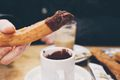 Cropped Image Of Person Dipping Churro In Chocolate At Table