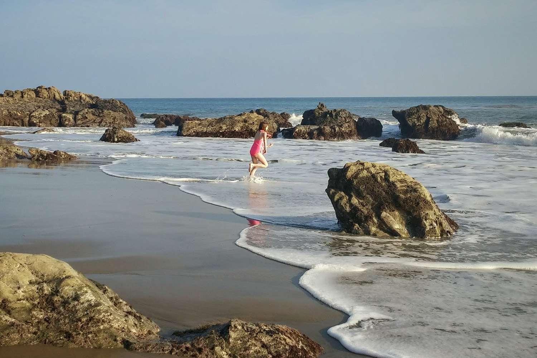 Girl Running into Ocean Rocks, Leo Carrillo Beach, Malibu, California