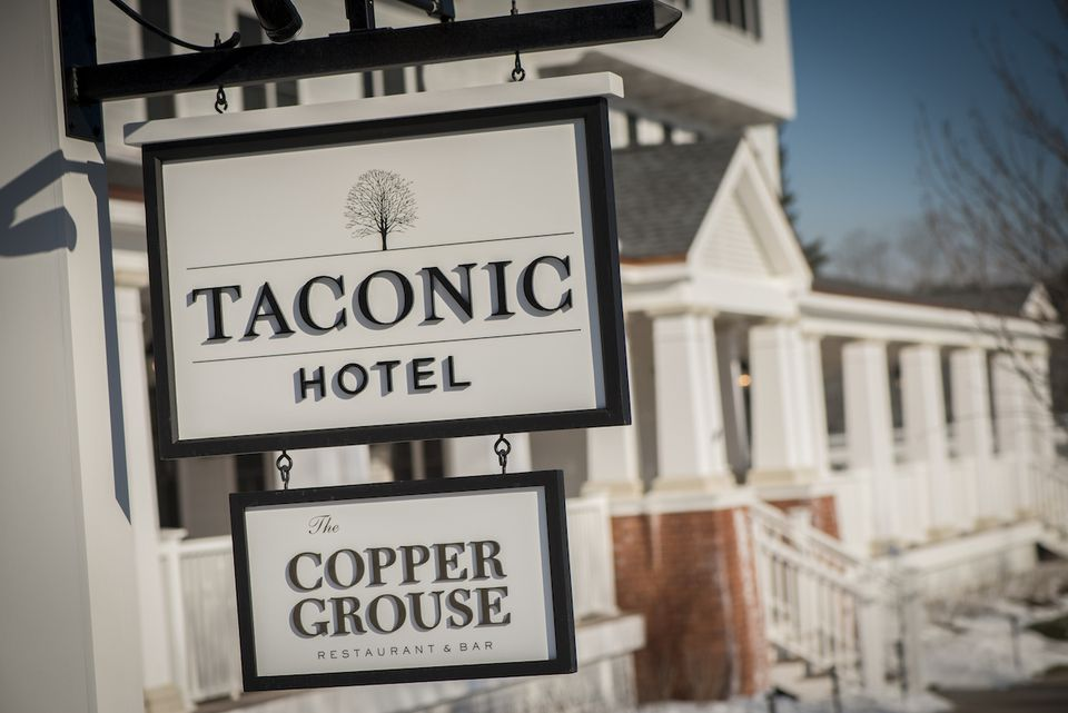 Taconic Hotel and The Copper Grouse Restaurant signs in front of the hotel in Manchester, Vermont.