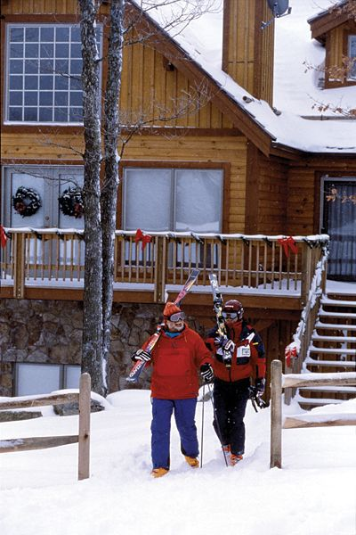 Two people carrying skis through snow