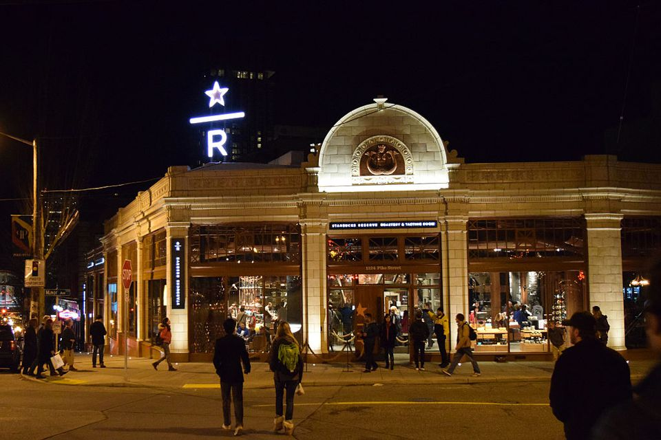 A view of the Starbucks Reserve Roastery & Tasting Room storefront, retail sign, and glowing logo at the newest concept store in the Capitol Hill neighborhood of Seattle, Washington. The sign glows white and heavy pedestrian traffic surrounds the store.