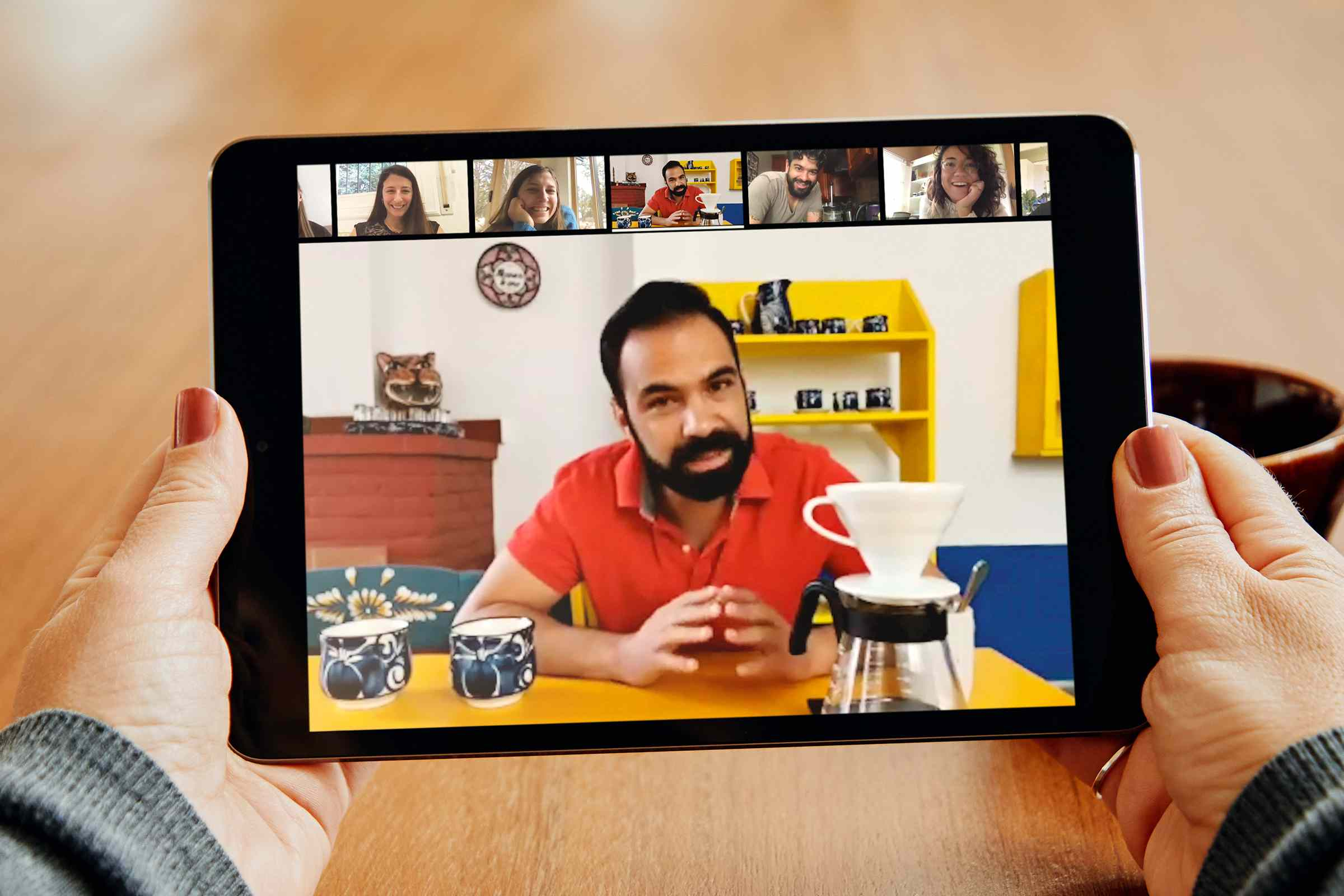 Someone holding a tablet with a virtual experience of a coffee class with a national coffee judge