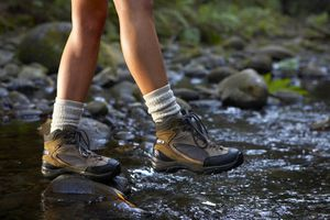 woman crossing stream wearing hiking boots