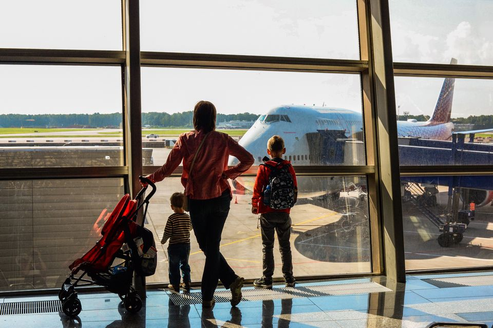 A family watching a plane at an airport