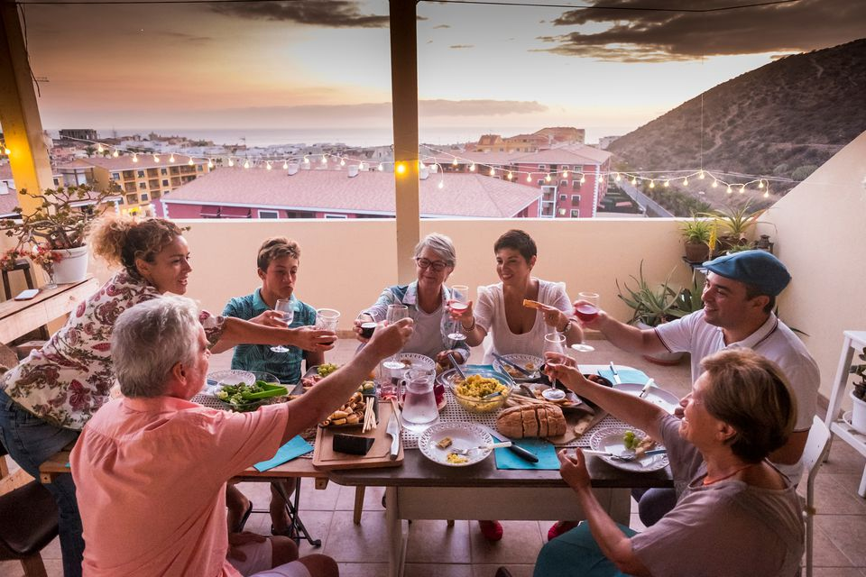 People eating tapas around a table on a rooftop