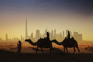 Tourists on camels watching a futuristic city