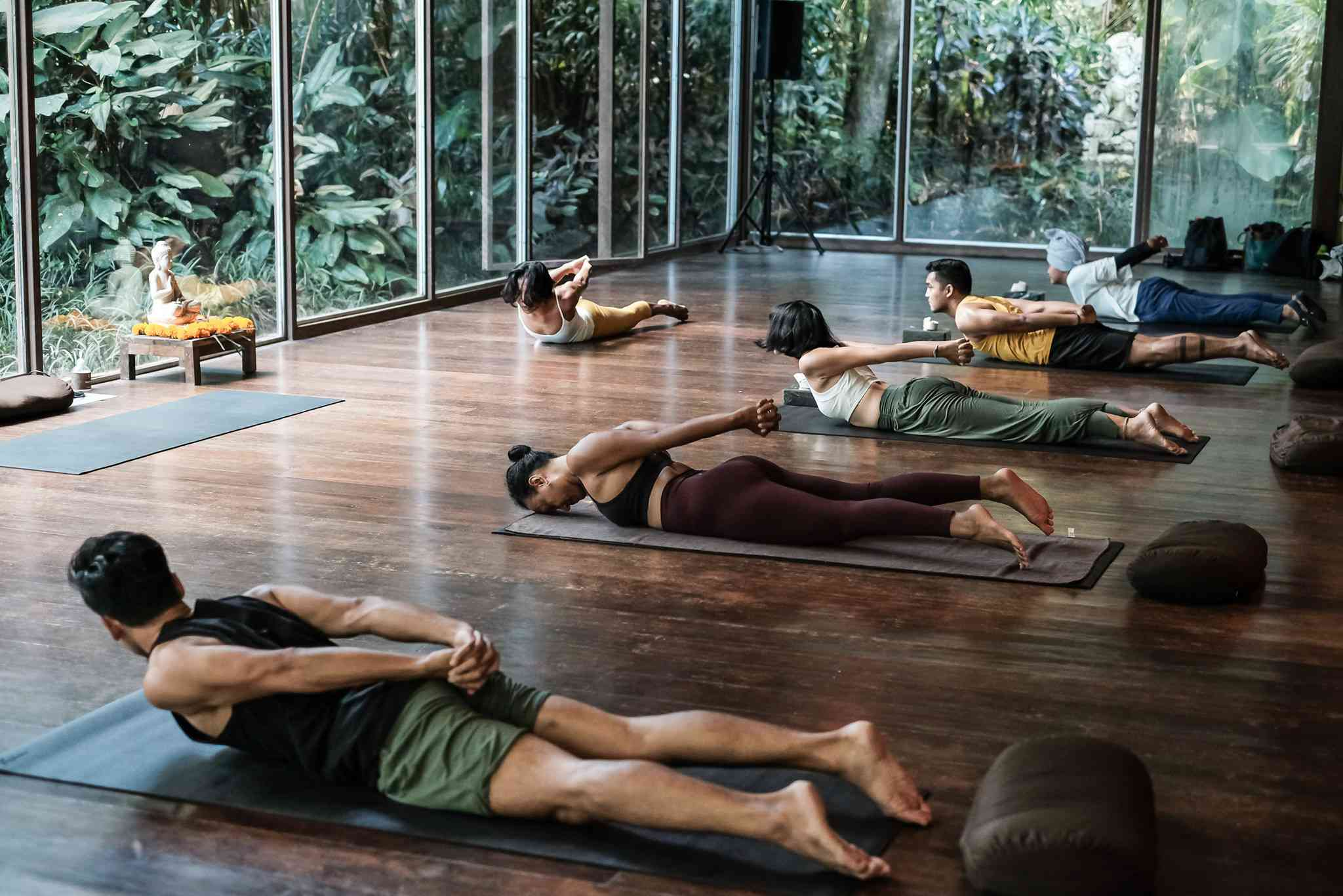 yoga class of five students and one teacher doing a variation of locust pose