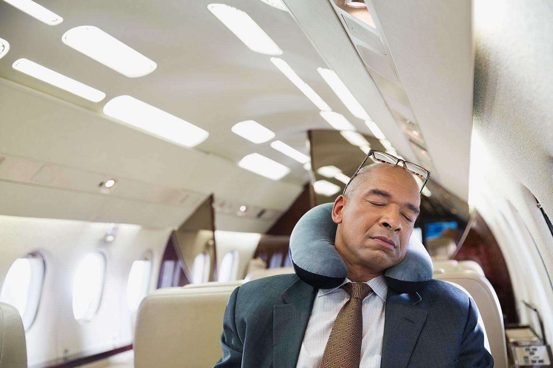 Hombre durmiendo la siesta con una almohada de viaje