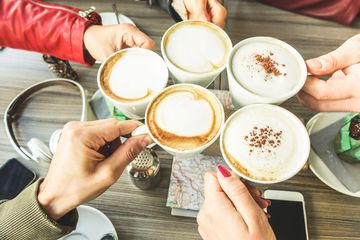 Cropped Hands Of People Toasting Coffee Over Table At Restaurant