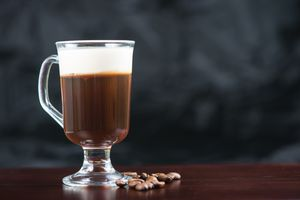 A strong Irish coffee in a glass on top of a wooden bar