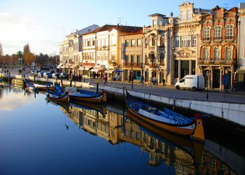 Yellow boats sit on the canal with typical Portuguese buildings in the background reflecting off the water