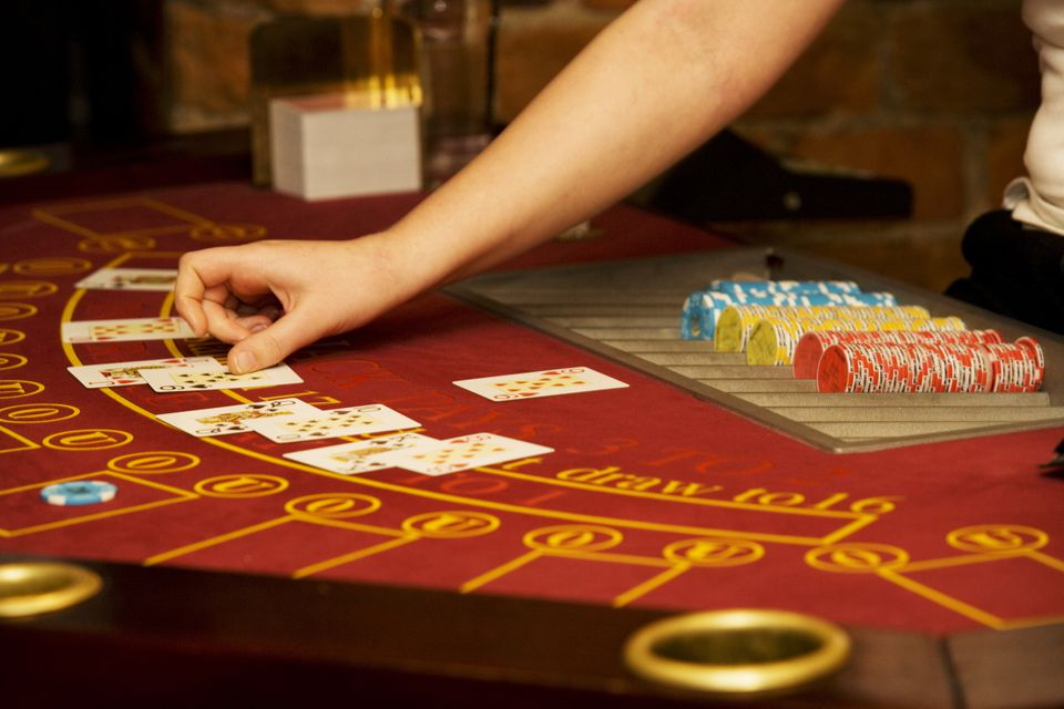 Casino worker's hand arranging cards on a poker table in a casino