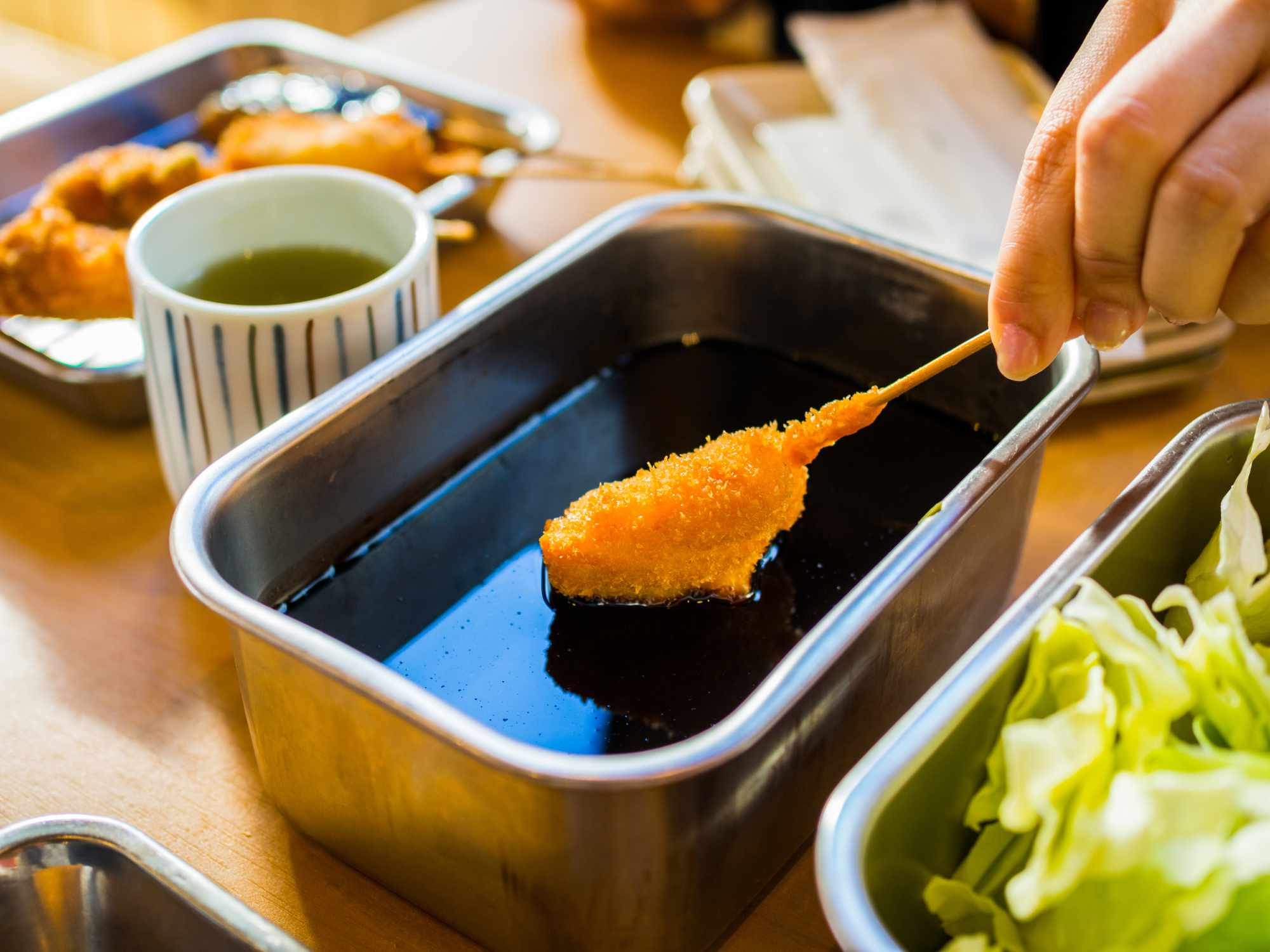 hand dipping a fried skewer into a metal container of a dark sauce
