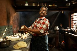 A cook making parothas (traditional, layered Indian pancakes in the kitchen of a small restaurant, Alumkadavu, Kerala, India