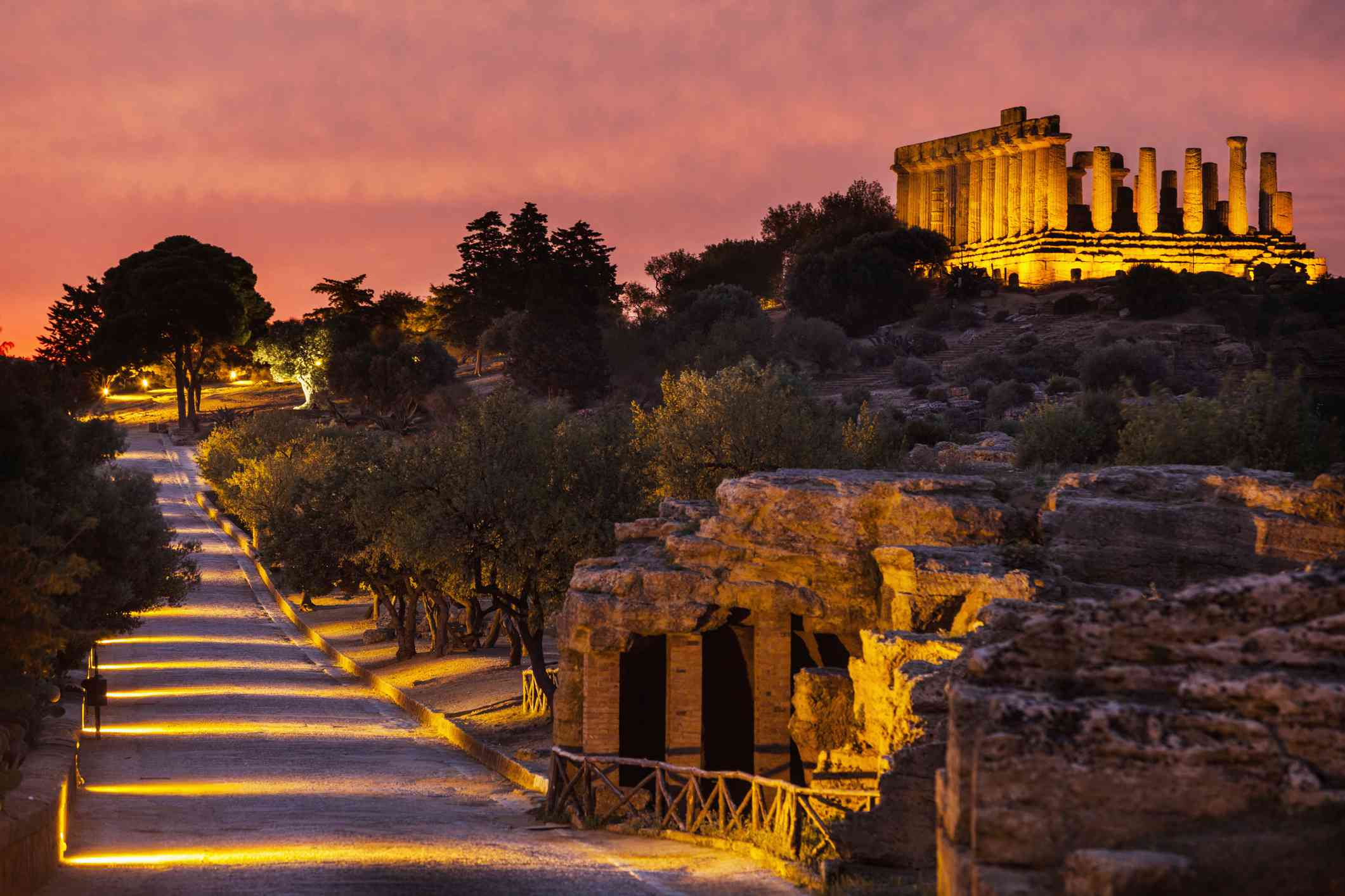 illuminated walkway to the Temple of Juno at dusk