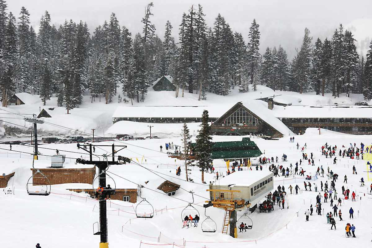 A mountain lodge sits at the base of the hill with dozens of skiers preparing to ride the lift.