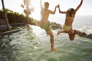 couple jumping hand in hand in pool