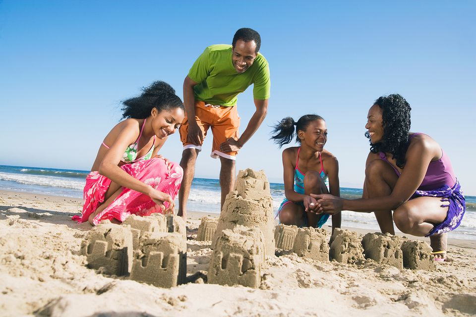 African American family building sand castles at the beach