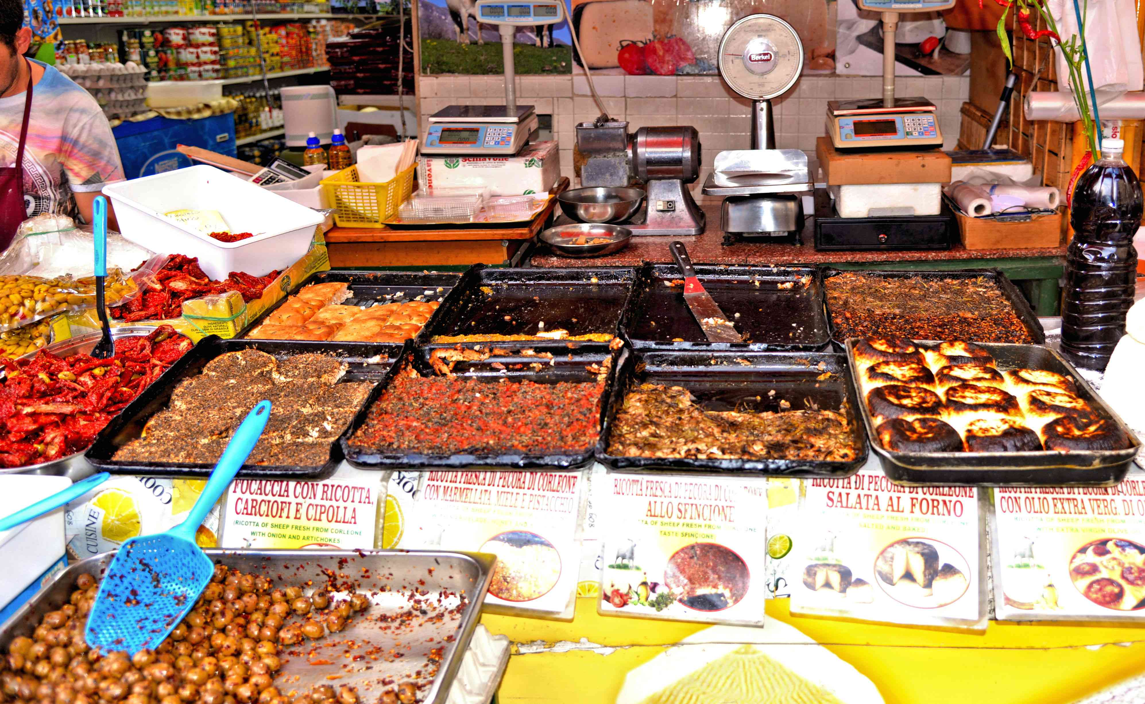 Various kinds of olives and any kind of local food and dishes at street market Ballarò in Palermo
