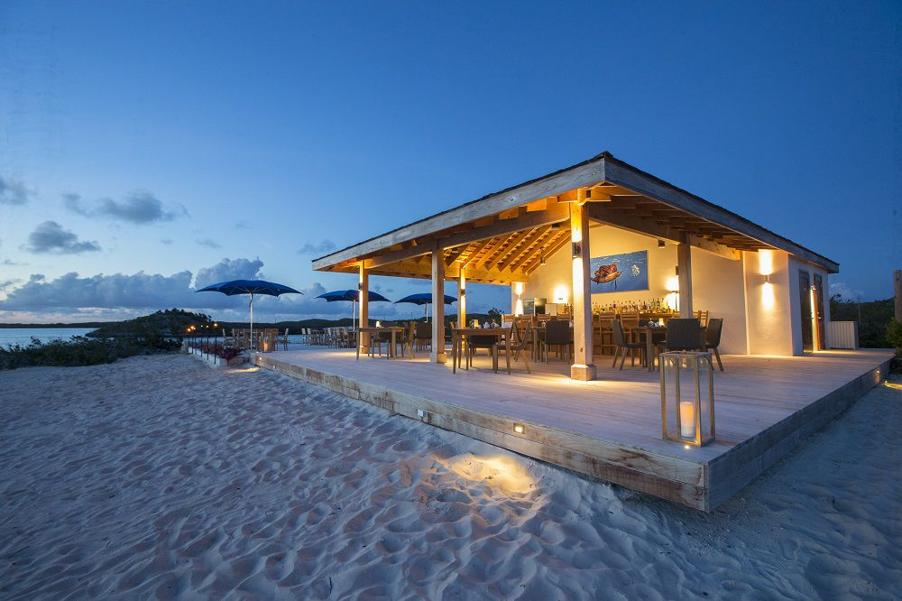 Covered beach bar with lights photographed at dusk