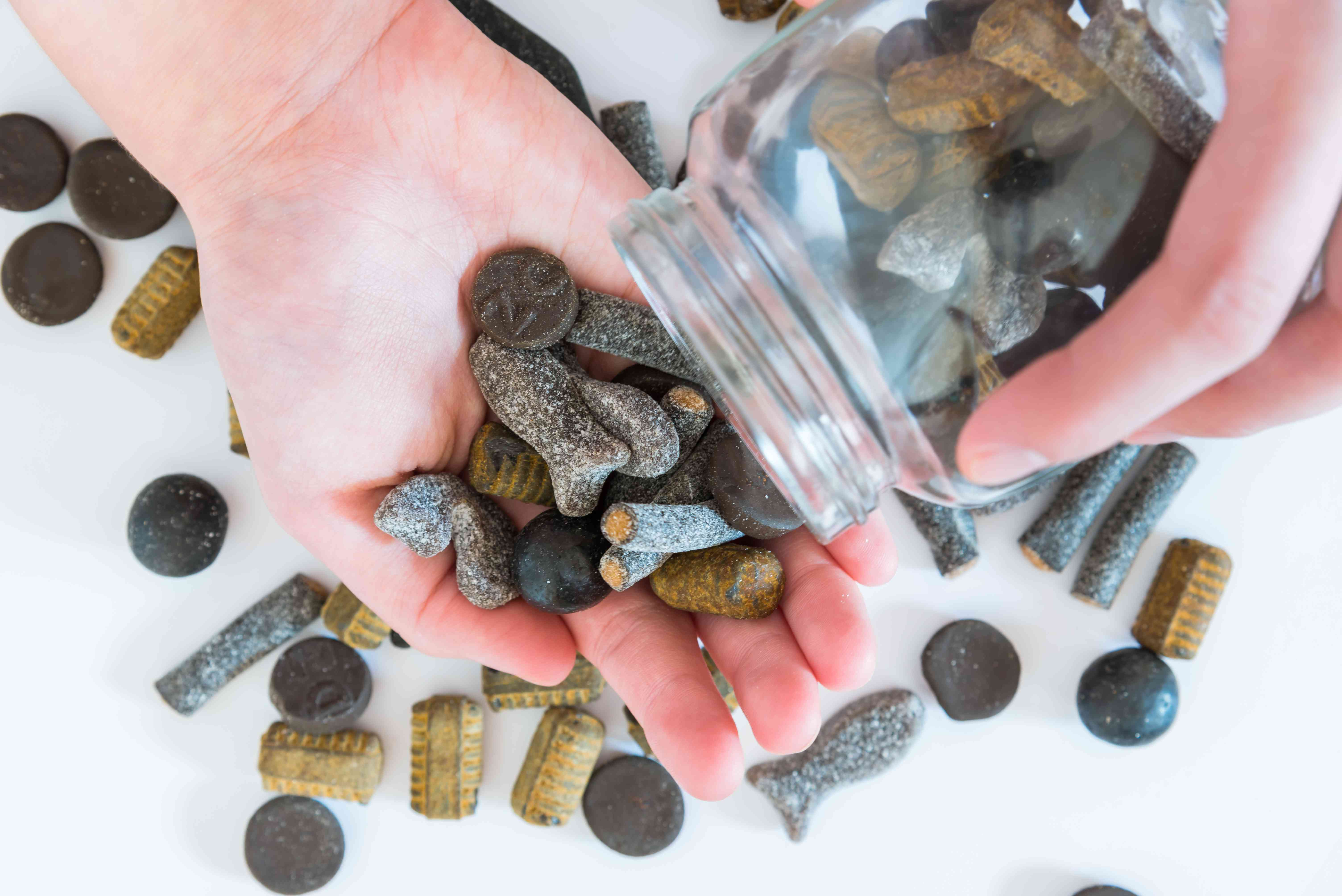 Assorted double salted licorice being poured from candy jar into woman's hand