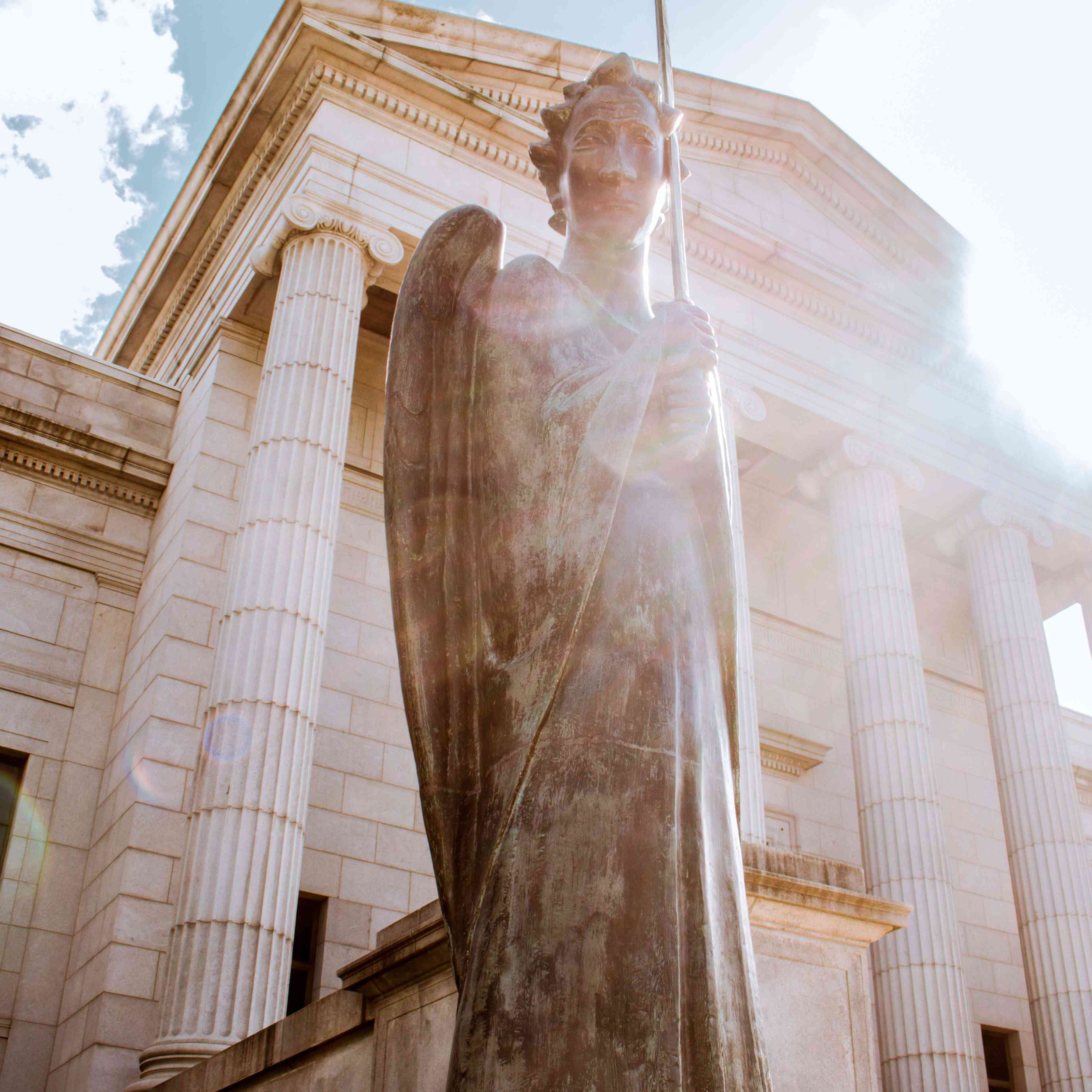 A statue of an angel with the sun peaking over the head in front of the Minneapolis Institute of Art