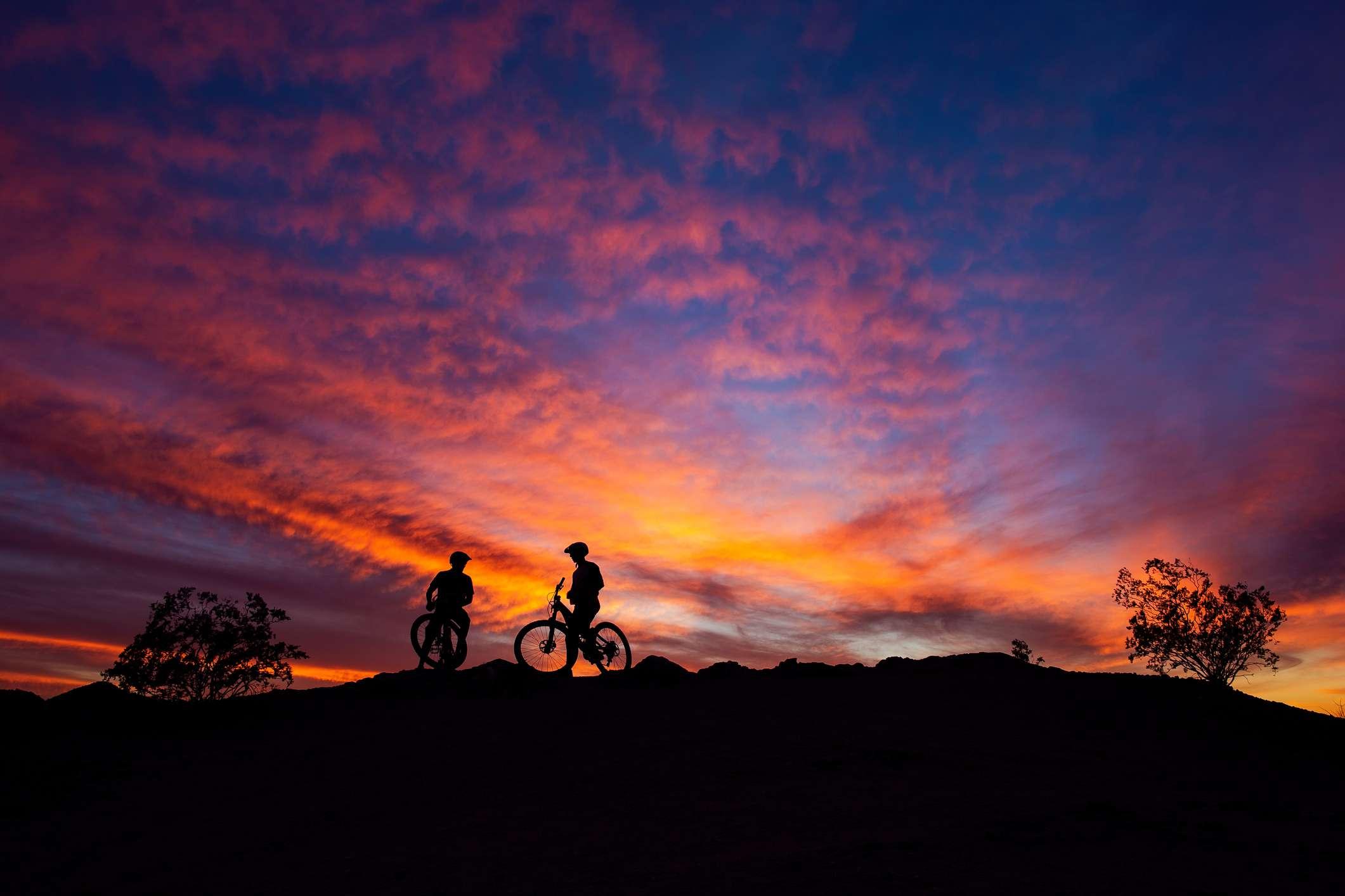 Ciclistas de montaña recortados contra una colorida puesta de sol en el desierto en South Mountain Park, Phoenix