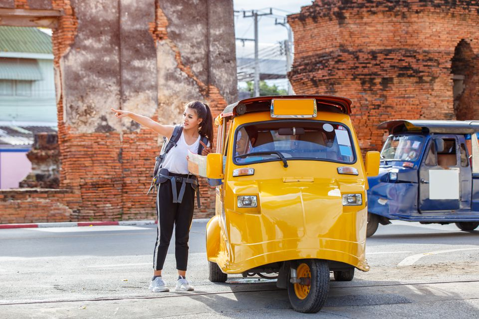 Traveler japanese girl hollding map travel query for the way with old man driver taxi or tuk tuk touring
