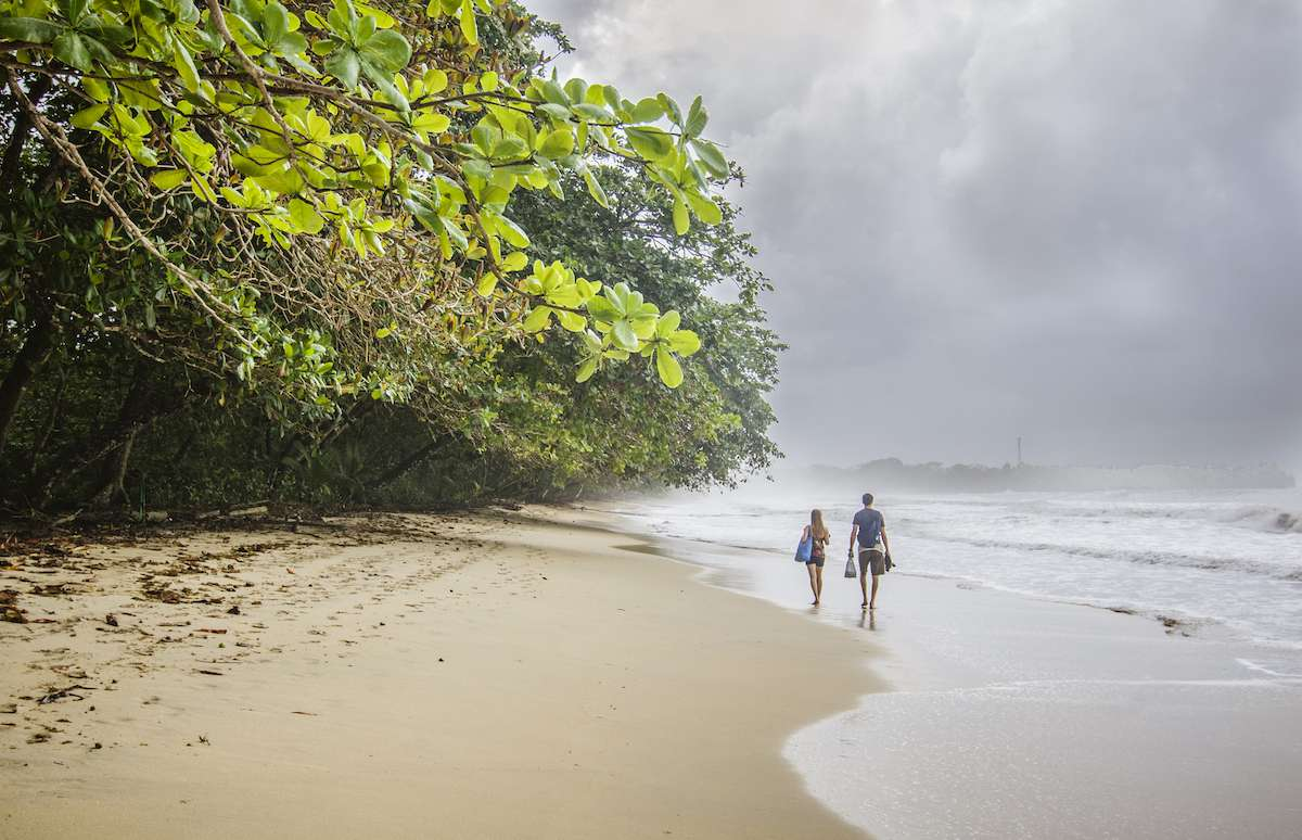Two people walking on a beach with trees close to shore at Cahuita National Park, Costa Rica