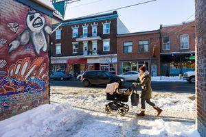 Woman pushing a stroller down a snowy street