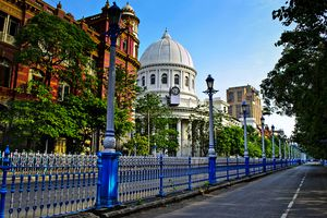 highly saturated street scene in Dalhousie, Kolkata with blue fencing in the foreground