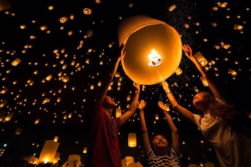 A family releasing a lantern for Loi Krathong during fall in Thailand