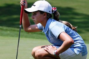 a young lady eyeing her golf ball on the green