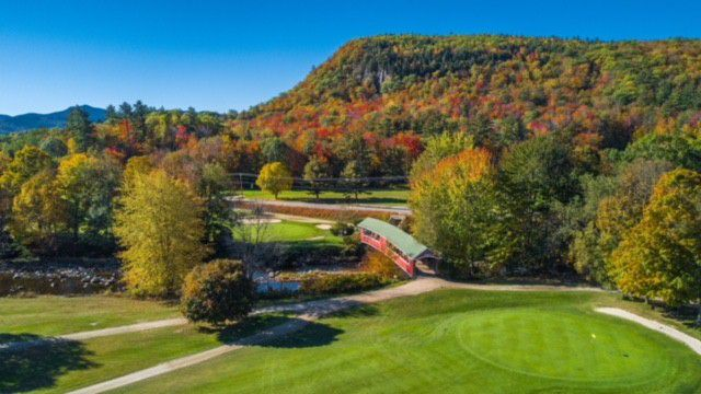 Aerial of golf course surrounded by fall trees