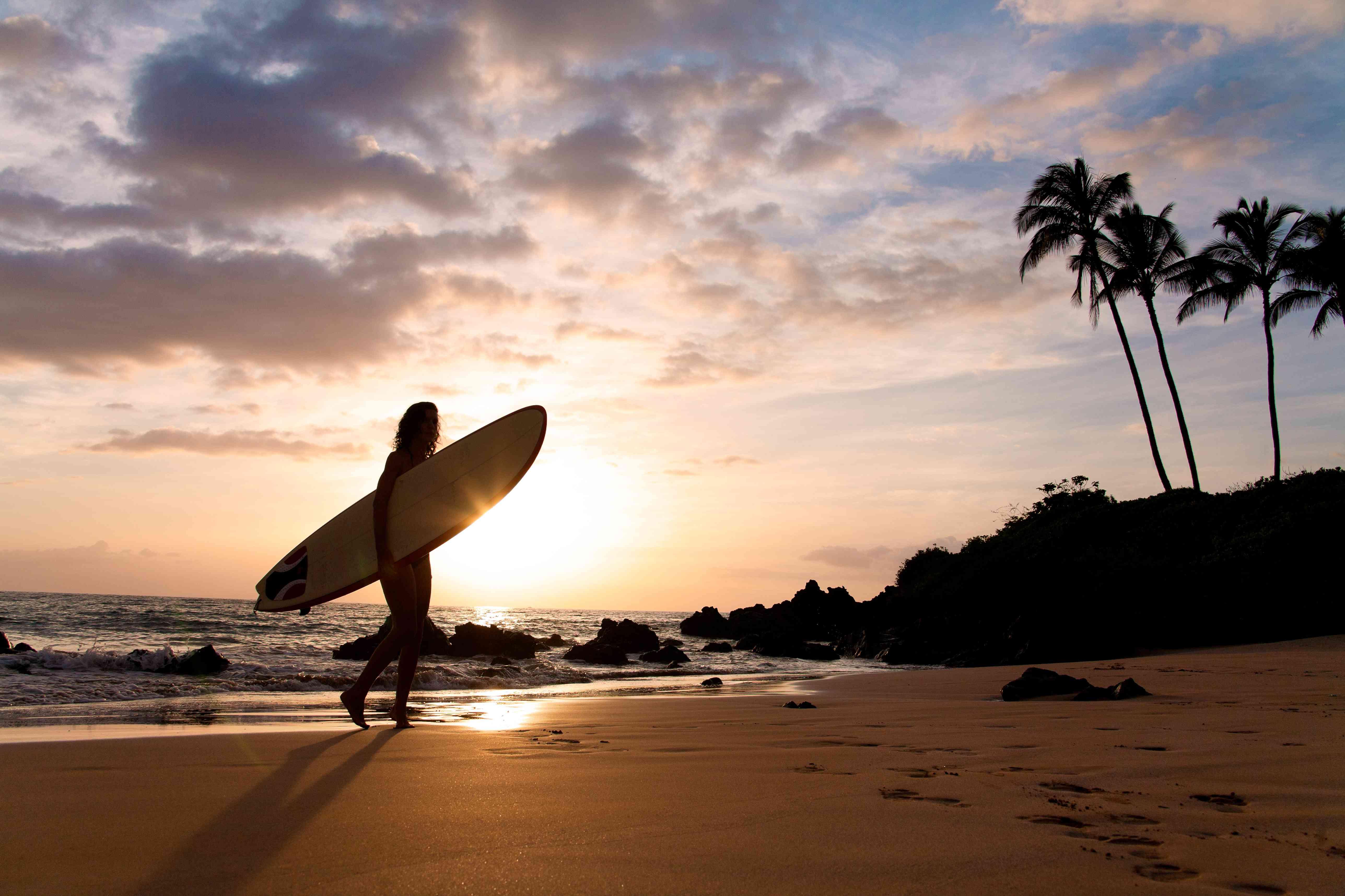 Surfer at sunet walkinh on sand