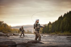 Two fly fishermen in a River one catching a fish