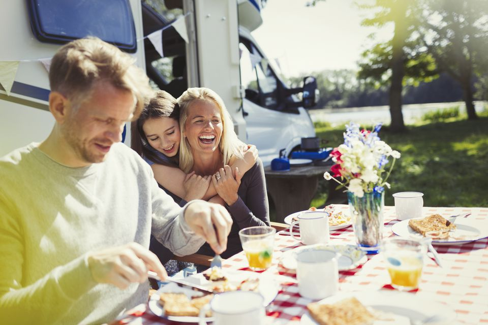 Happy family hugging and eating breakfast outside sunny motor home