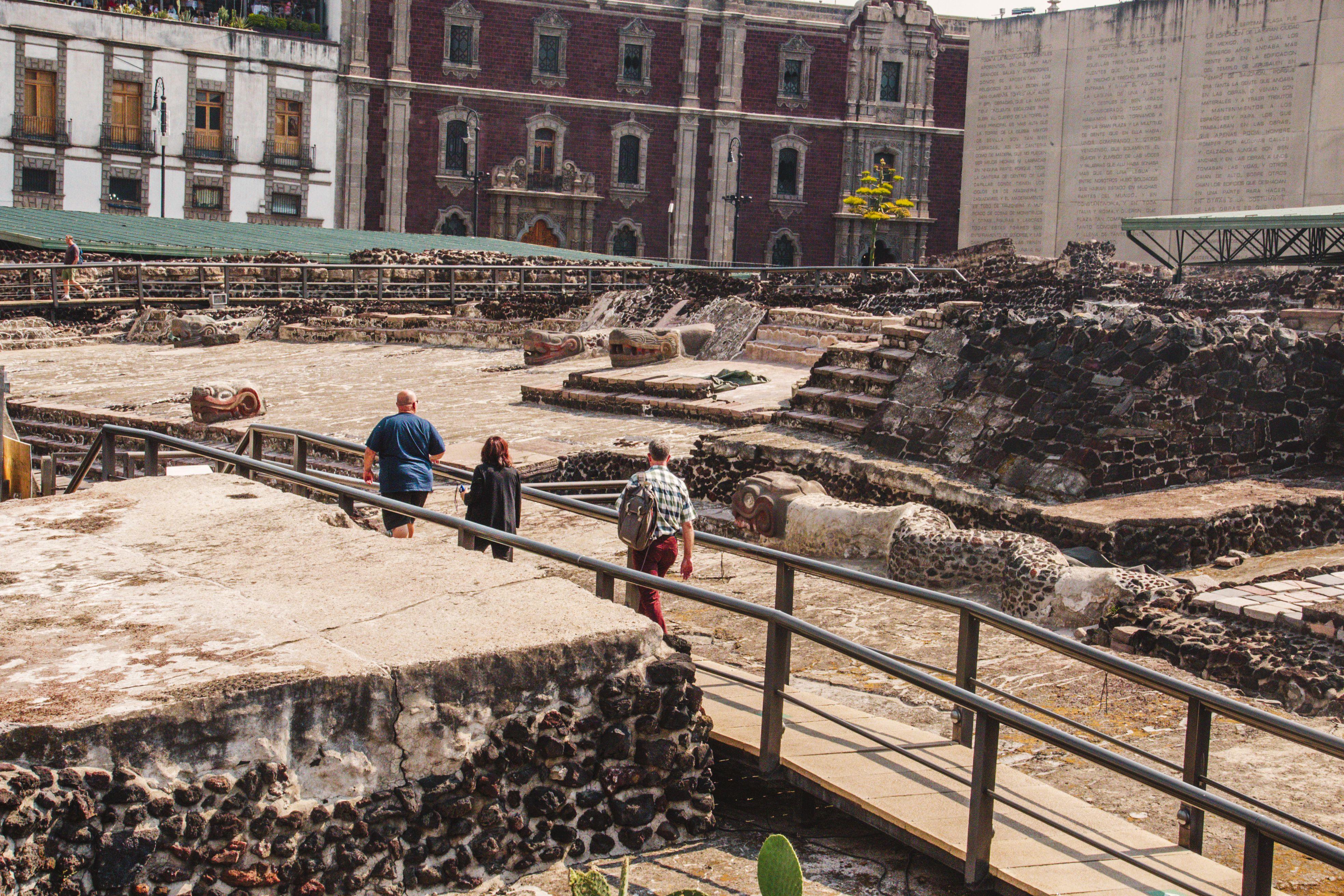Templo Mayor with three people walking on a bridge