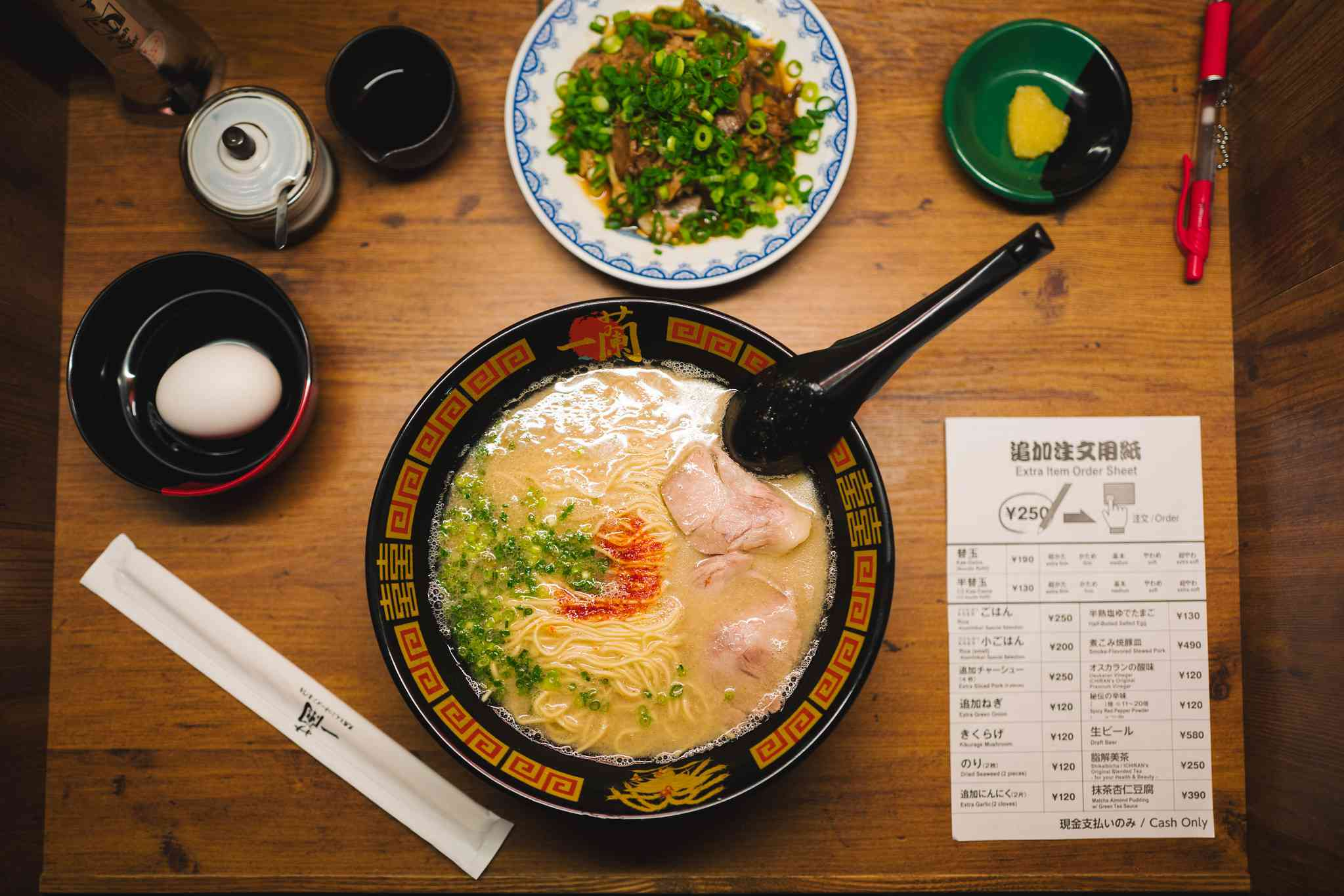 Overhead image of ramen, a boiled egg, and order sheet on a table at Ichiran