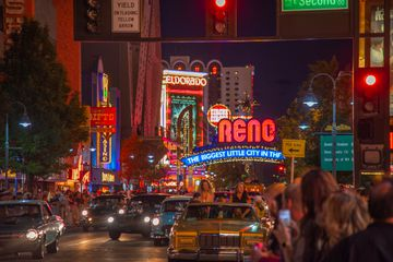 Cars driving down the main strip in Reno with view of the Reno sign behind them