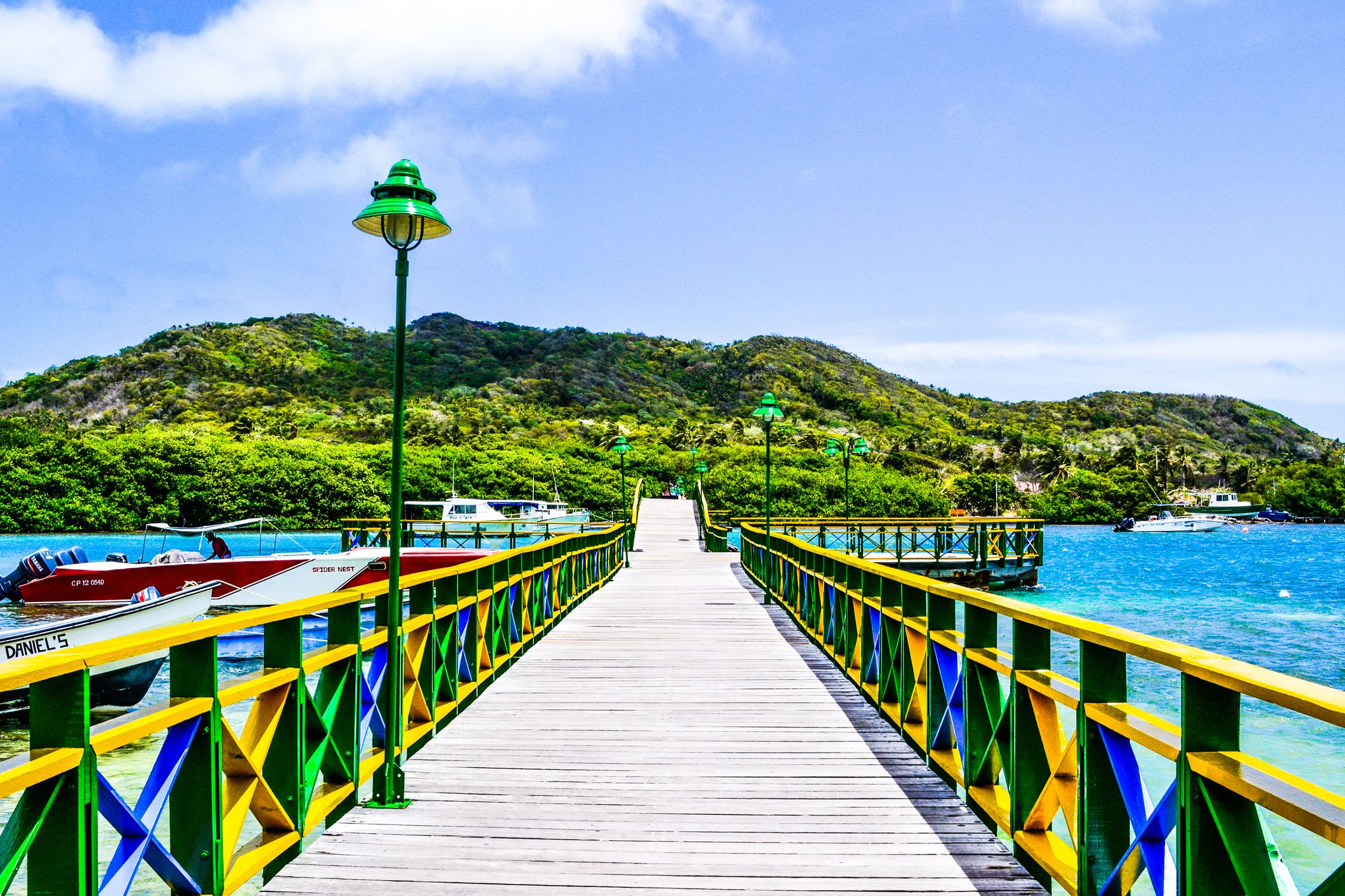 Scenic View Of Jetty Next To Hill Against Cloudy Sky