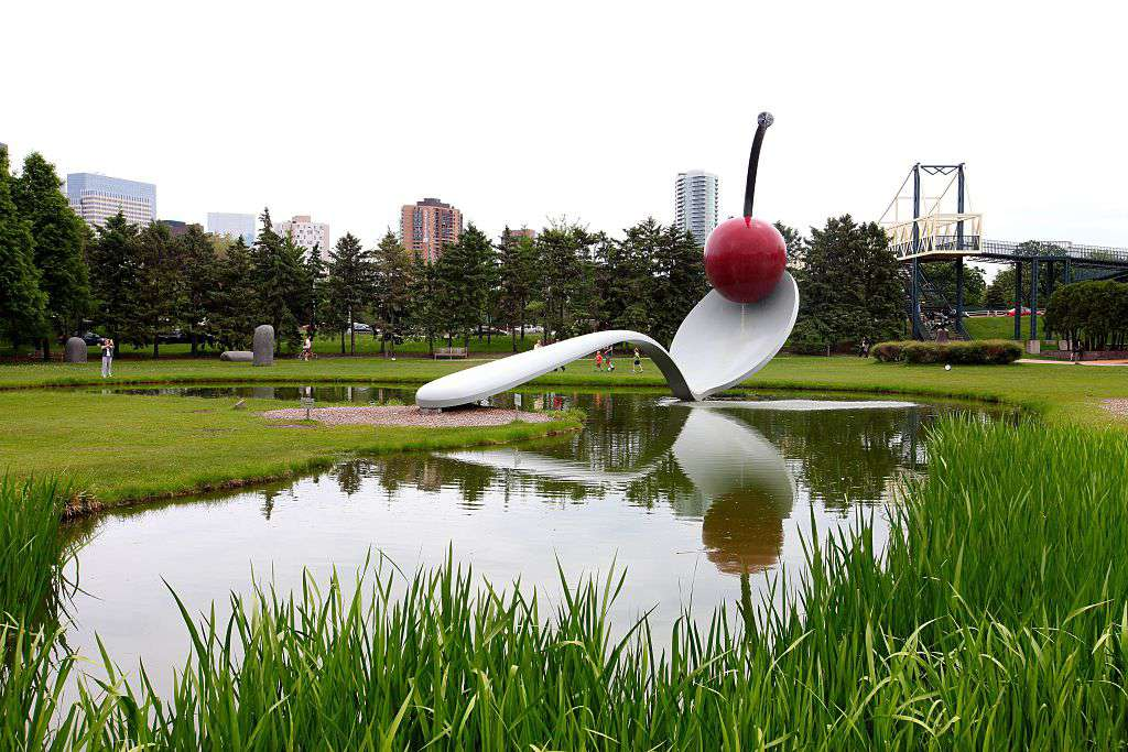 a sculptural fountain shaped like a bent spoon with a cherry balancing on top