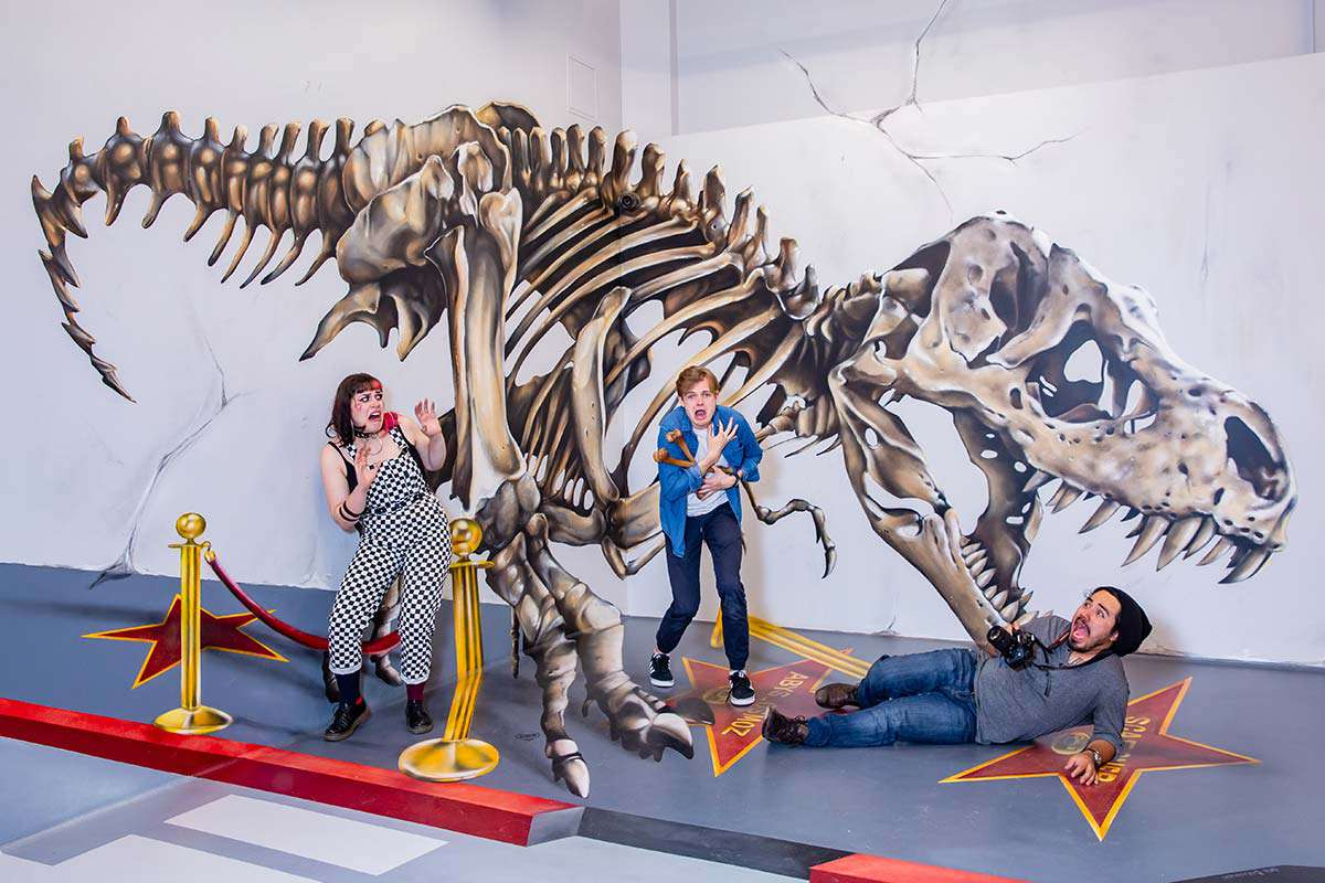 three people posing in front of an optical illusion of a t rex skeleton